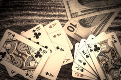 Two pairs and three of a kind vintage poker cards with money on a wooden background Stock Images