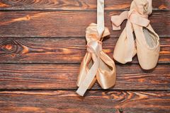 Two pairs of ballet shoes. Two pairs of traditional ballerina dancing shoes - old and new - hang on wooden background. After ballet show concept. Place for text Stock Photo