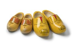 Two pairs of traditional yellow Dutch wooden shoes. Isolated on white background Stock Photo