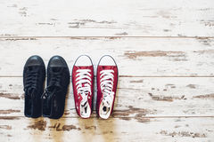 Two pairs of trainers, red and black, on wooden floor top view. Two pairs of trainers, red and black side by side on wooden floor top view Stock Photography