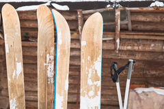 Two pairs of wide skis. And log house wall in winter day Stock Photos