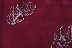 Two pairs of wire hearts. Two pairs of metal wire hearts on a velvet red background Royalty Free Stock Photo
