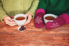 Two pairs of women hands knitted mittens holding a cup on a wooden background. stock photos