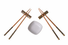 Two pairs of wooden chopsticks and white saucer. Two pairs of wooden chopsticks and white empty saucer. Sticks are decorated with temple theme ornamentation Stock Images