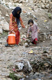 Two Pakistani children bringing water. Two little girls bringing drinking water from a long distance in a water cooler stock photo