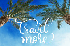 Two palm treetops against a sunny sky and Travel more text. Calligraphy lettering hand draw Royalty Free Stock Image