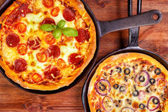 Two pan pizzas. Two fresh pan pizzas on iron skillets , wooden background , top view Royalty Free Stock Images