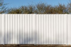 Two panels of a white metal fence around wooded area. Two panels of a white metal fence used to screen off a wooded site stock photos