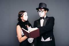 Two pantomime theater performers posing with book. Mime actor and actress performing Royalty Free Stock Photos