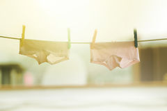 Two pants of twin babies hanging on a cord of a terrace in a peaceful village. Stock Images
