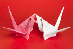 Two paper birds. Facing each other on a red background. Shallow depth of field Stock Photo