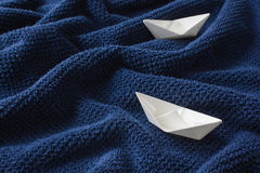 Two paper boats on blue wavy cotton fabric Royalty Free Stock Image