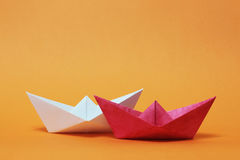 Two paper boats, competition. Competition between two paper boats. Red and white ships sailing on orange background. Rivalry, business, success and efficiency Royalty Free Stock Image