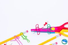 Two paper clips talking, sitting on a zigzag scissors and two lying and talking on pencil. Miniature school life and back to schoo stock image