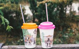 Two paper coffee cup special for girls on green background, outdoors Royalty Free Stock Images