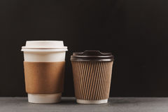 Two paper coffee cups. Two different paper coffee cups on the table. Dark background with place for text. Place for yur logo on cup holders Stock Image