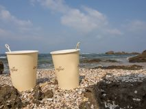 Paper cups with coffee on the background of the sea. Two paper cups with coffee on the seashore against a cloudy sky background Stock Images