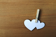 Two paper heart pinch by clip on wooden bg Royalty Free Stock Photos