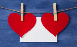 Two paper hearts and card hanging on a rope Royalty Free Stock Photo