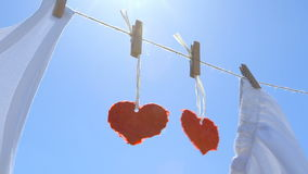 Two Paper Hearts on a Clothesline - symbol for love - camera pan stock video footage
