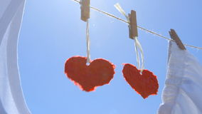 Two Paper Hearts on a Clothesline - symbol for love - camera pan stock video