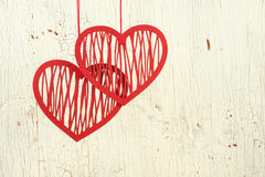 Two paper hearts on a  old  white wood. Tw openwork  paper hearts  on a  old  white wood Royalty Free Stock Image