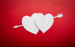 Two paper hearts pierced with an arrow symbol for Valentines day Stock Photos