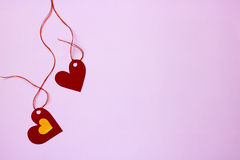 Two paper hearts tide to a string on a pink background Royalty Free Stock Image
