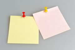 Two paper sheets with office buttons on gray. Two paper sheets attached with yellow and red office buttons on gray background Royalty Free Stock Photos