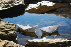 Two paper ships in the puddle Stock Images