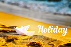 Two paper white ships on the sand near the sea.Inscription holiday against the backdrop of sand and sea Stock Photos