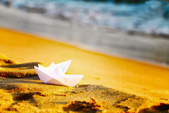 Two paper white ships on the sand near the sea.White crafts origami handmade on the beach on a background of waves stock image