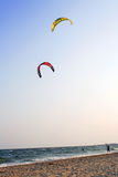 Two Parachutes in the sunset. Red and yellow parachutes in the sunset above sand and sea Stock Images