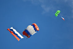Two parachutists gliding with russian flags on blue sky background. Two parachutists gliding with russian flags Royalty Free Stock Image