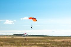 Two parachutists are landing on colorful parachutes to aerodrome.  stock photography