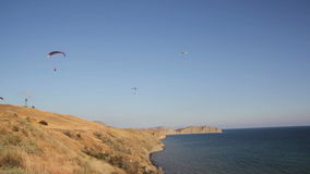 Two paraglider above hills and sea. Two paraglider above the bay with mountains stock video footage