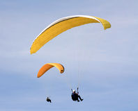 Two Paragliders. With yellow gliders in a blue sky Stock Photos