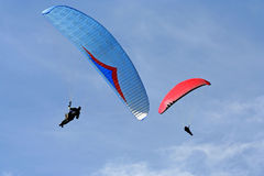 Two paragliders. Paragliders in flight above hills and countryside Royalty Free Stock Images