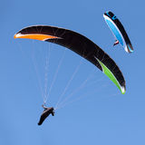 Two paragliders in flight against blue sky Stock Photography