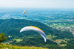 Two paragliders fly over the hills on a sunny day Royalty Free Stock Photos