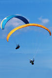 Two Paragliders flying over mountains in summer day Stock Photography