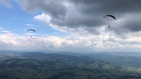 Two paragliders are flying in the sky above the mountains. Two paragliders are flying in the sky above the mountains against the backdrop of amazing clouds stock video