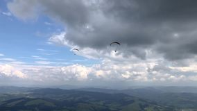 Two paragliders are flying in the sky above the mountains. Two paragliders are flying in the sky above the mountains against the backdrop of amazing clouds stock video footage