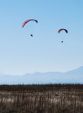 Two Paragliders on sky. Two para-gliders soar over mountains and earth Stock Photo