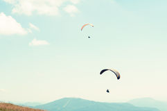 Two paragliders in sky with hills in background Stock Images