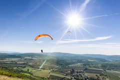 Two paragliders under the rays of a white sun Stock Photo