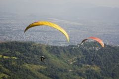 Two paragliders on yellow and red parachutes on the background of green mountains and a city in the valley. A Two paragliders on yellow and red parachutes on the royalty free stock image