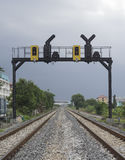 Two parallel railway pass in a city with a railway traffic light Stock Photo