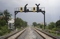 Two parallel railway pass in a city with a railway traffic light Royalty Free Stock Photography