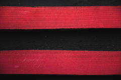Two parallel red stripes. Wooden texture on black wooden texture Stock Images
